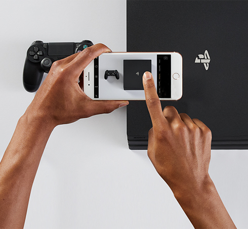 Person taking a photo of a Playstation and controller