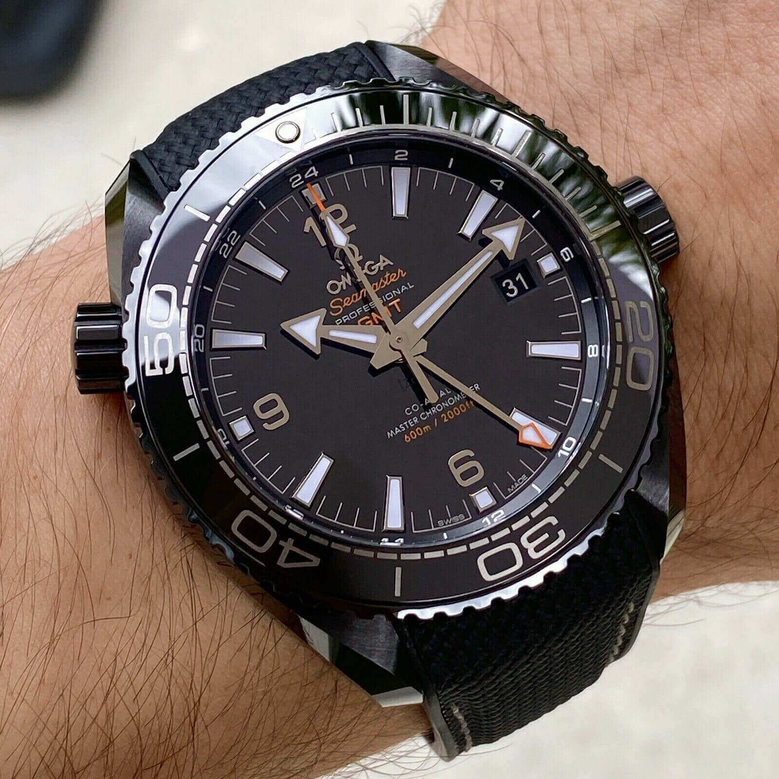 A black  Omega Seamaster Planet Ocean watch with a black face.