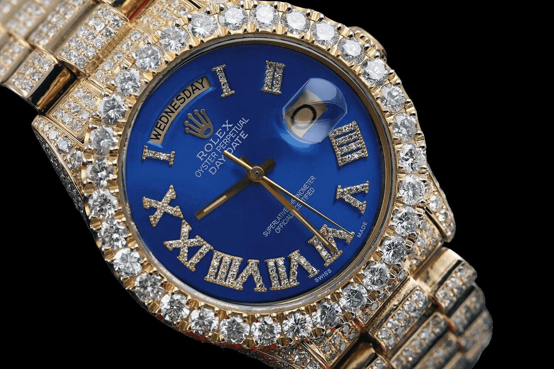 A golden Rolex watch with a blue  dail.