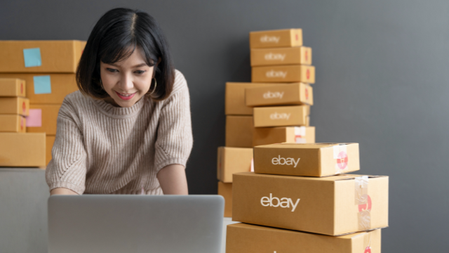 A smiling woman standing at a table, looking at her laptop, with boxes around her.