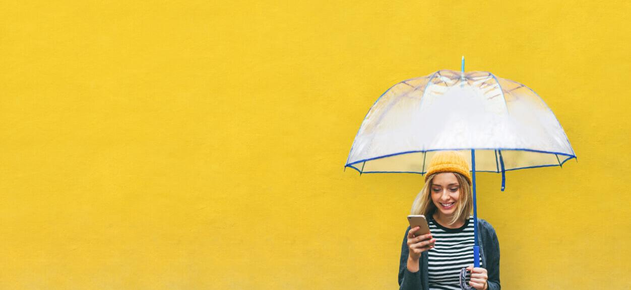Frau schaut mit Regenschirm auf ihr Smartphone