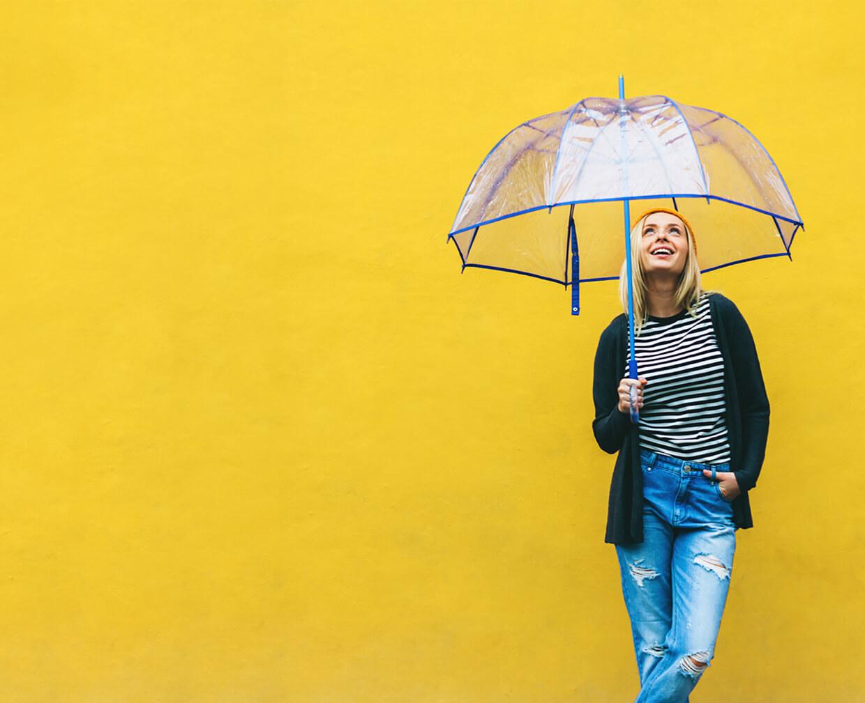 Frau mit blauem transparentem Regenschirm auf gelbem Grund