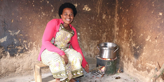 Eine Frau aus Ruanda sitzt neben ihrem Kochofen