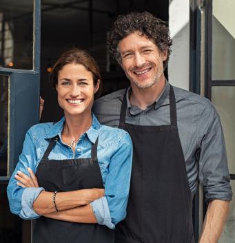 Kleinunternehmer vor ihrem eröffneten Geschäft