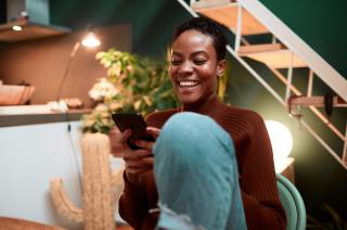Mujer feliz comprando online con su móvil con variedad de opciones de pago