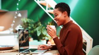 Mujer feliz comprando online con su portátil y una taza de café