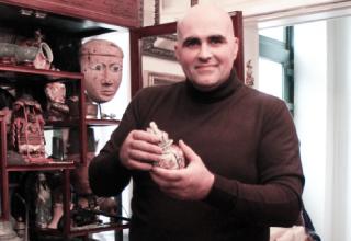 Un homme tenant un petit objet en céramique.