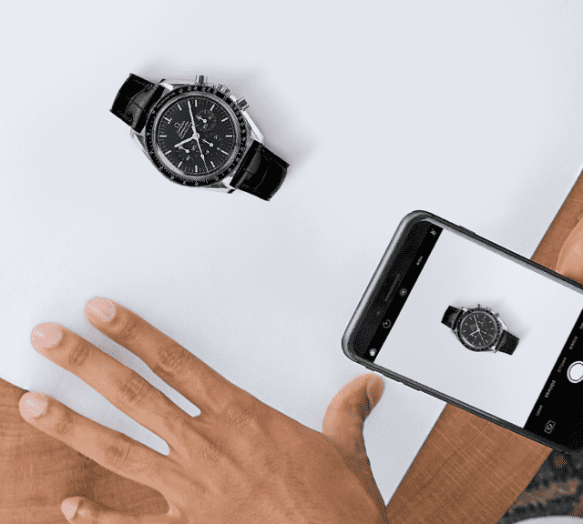 A person taking a picture of an OMEGA watch in a box.