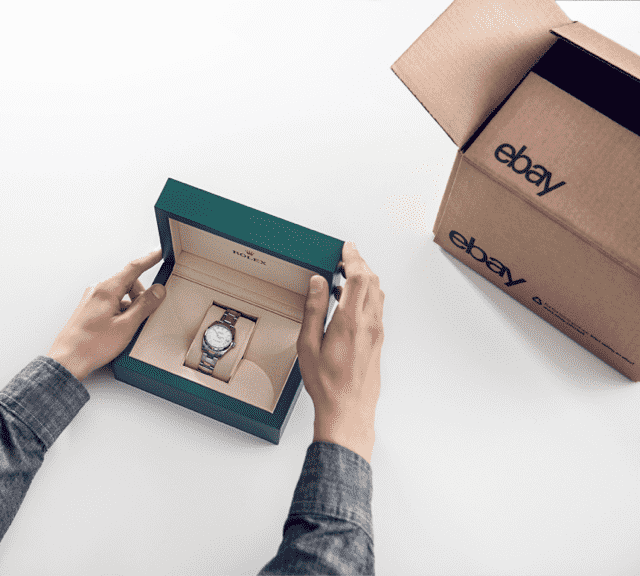 Person unboxing a Rolex watch from an eBay package.