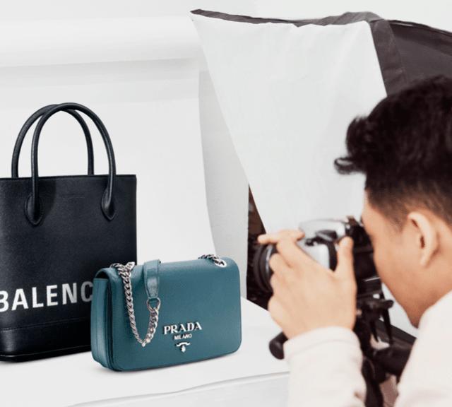A person taking a photograph of a Balenciaga bag and a Prada bag.