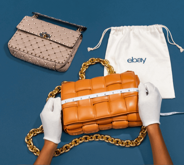 A person wearing gloves measuring a brown purse. Another purse and an eBay branded dust bag lie to the side of and behind the purse being measured.